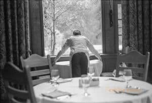 A server lays down a new white tablecloth in a hotel dining room with her back to the camera. She is in front of a window framed by curtains on either side. In the foreground is a table set for a meal.