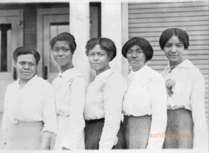 Five African American women stand in a line, facing the camera, in the early 1900s.