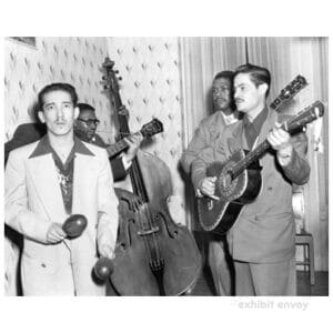 Four men stand in the corner of a house playing instruments. One holds maracas while three play guitars. A bass rests against the wall in the background.