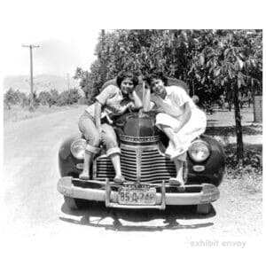 Two young Filipinas sit on the hood of an old car. They are in a rural area with a dirt road and trees.