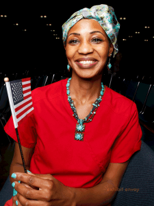 An African woman wears an American flag pin and smiles towards the camera.