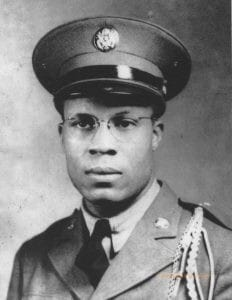 An African American man wears an army uniform, hat, and glasses in a formal portrait.
