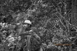 A park ranger stands amongst trees. A bear skin is wrapped around his upper body.
