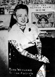 A tattooed woman sits with her legs crossed. Tattoo flash is on the wall behind her.