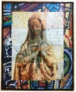 A quilt with a graffiti border surrounds an image of a Madonna statue.
