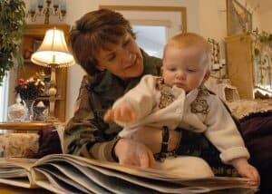 A woman points to a book while holding a baby in her arms in a living room. The woman wears an army uniform.