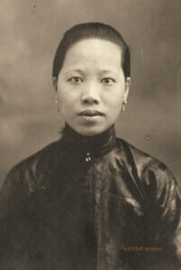 An Asian woman looks at the camera in an old photograph.