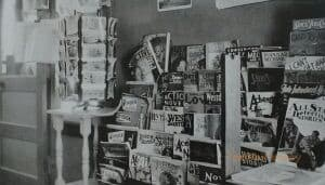 Interior of a post office with a postcard rack and magazine rack.